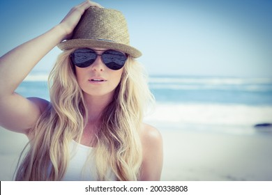 Stylish blonde looking at camera on the beach on a sunny day