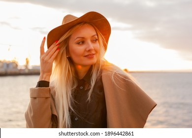 Stylish blonde woman in felt hat and coat at sunrise at sea