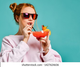 Stylish blonde woman in modern red sunglasses drinks sips through straw a strawberry margarita cocktail on blue mint background