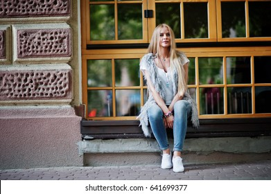 Stylish blonde woman wear at jeans and girl sleeveless with white shirt against windows at street. Fashion urban model portrait.