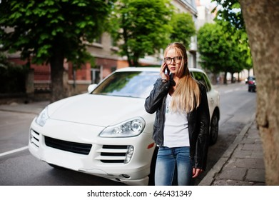 Stylish blonde woman wear at jeans, glasses and leather jacket with mobile phone, against luxury car. Fashion urban model portrait.
