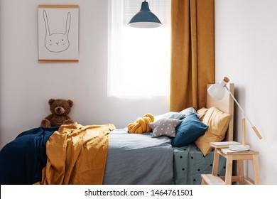 Stylish blue and orange kid's bedroom design in bright apartment
