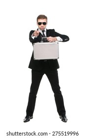 Stylish bodyguard with metal suitcase pointing his forefinger at viewer. Full length. Isolated over white background