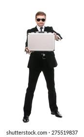 Stylish bodyguard presenting metal suitcase. Full length. Isolated over white background