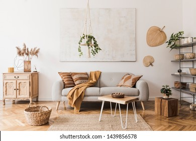 The stylish boho compostion at living room interior with design gray sofa, wooden coffee table, commode and elegant personal accessories. Honey yellow pillow and plaid. Cozy apartment. Home decor - Shutterstock ID 1439856578