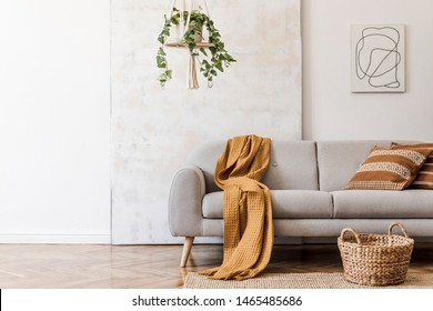 The stylish boho compostion at living room interior with design gray sofa, rattan basket, mock up paintings and elegant personal accessories. Honey yellow pillow and plaid. Cozy apartment. Home decor