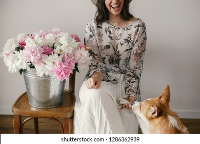 Stylish boho girl playing and smiling with cute golden dog at metal bucket with peonies on rustic wooden chair in home. Beautiful hipster woman having fun with her doggy. Friendship