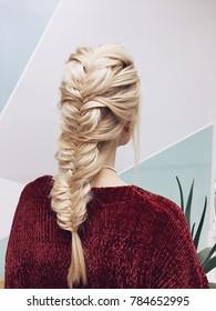 Stylish boho hairstyle. Blonde girl in red sweater isolated on geometric light background. Wedding braid.