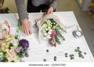 Stylish bouquet of roses, pineapple decorative, eucalyptus on a white table with space for text