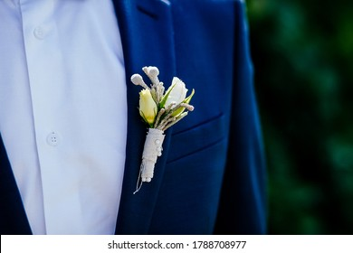 stylish boutonniere on the groom's jacket, wedding day, beautiful flower boutonniere, wedding concept