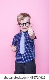 Stylish boy in shirt and glasses with big smile. Ok. School. Preschool. Fashion. Studio portrait over pink background
