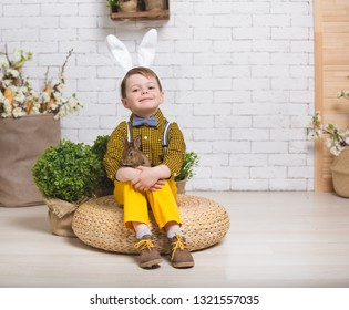 Stylish boy in yellow pants and with ears of the Easter Bunny. The child holds the little rabbit in his arms