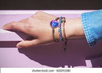 Stylish bracelets on female hand - top view
