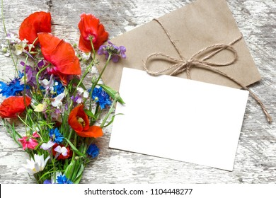 Stylish branding mockup to display your artworks. blank greeting card or wedding invitation with summer wildflowers on wooden background. flat lay