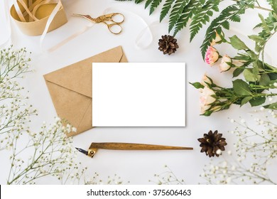 Stylish branding mockup with flowers to display your artworks. Cute vintage mock up on wooden background.