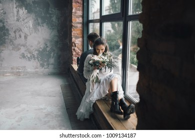 Stylish bride with bouquet sits on the windowsill next to the groom. Artwork. Copy space