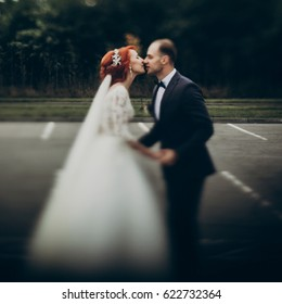stylish bride and groom kissing on background green trees, holding hands. luxury wedding couple newlyweds first kiss, happy emotional moment. space for text. true feelings