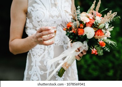 Stylish bride with wedding bouquet flowers and hold in hands glass of champagne, drinks. On the background nature in courtyard of house. Wedding ceremony. Close up