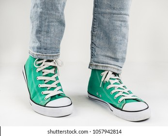Stylish, bright, green sneakers and funny, happy socks on a white background. Sport, style, beauty, good mood