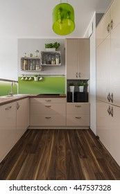 Stylish and bright kitchen interior design in beige and green with elegant wooden floor