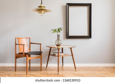 Stylish and bright retro interior with design chair , gold lamp and small table with vase. Black mock up frame on the gray background wall. Minimalistic concept of sitting room. Real photo.
