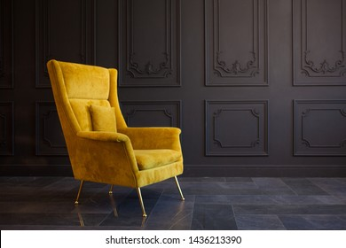 Stylish bright yellow chair against a dark gray wall. Stylish chair on wall background in classic interior, copy space, fashionable interior