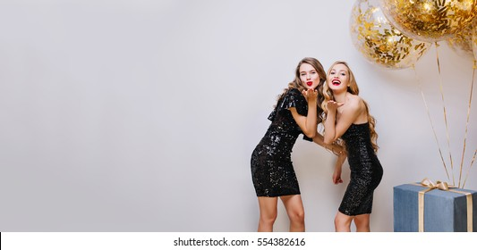 Stylish brightful image of two joyful attractive women celebrating party in luxury black dresses on white background.curly hair, red lips, big golden balloons with tinsels, presents.Place for text
