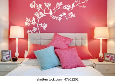 Stylish brightly decorated modern bedroom with wall mural and cushions