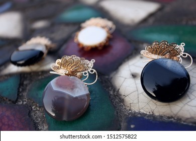A stylish brooch and pendant made of round agate stone, combined with metal-plated modern jewellery, placed on a ceramic tabletop.