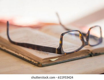 stylish brown reading glasses sitting on old book and wooden table.