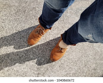stylish brown shoes boots for men and blue jeans outdoors on granite floor. casual look. look down on the legs and feet. fashionable combination