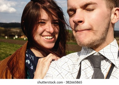 stylish brunette beautiful woman and man in love having funny photos in windy spring field
