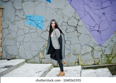 Stylish brunette girl in gray cap, casual street style on winter day against colored wall.