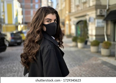 Stylish brunette woman in a black protective mask stands on empty sunny city street during COVID-19 quarantine. She wears a black trench coat with a white shirt. Horizontal.