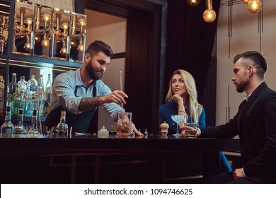 Stylish brutal barman serves an attractive couple who spend an evening on a date.