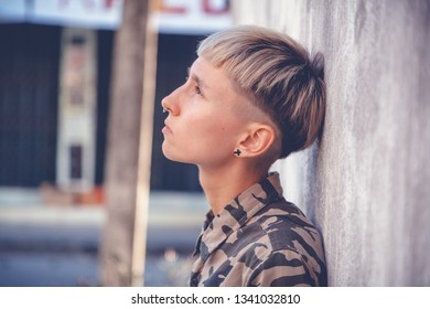 Stylish brutal young woman with short hair and shaved temples with on background of the city, rebel and millennial, generation Z