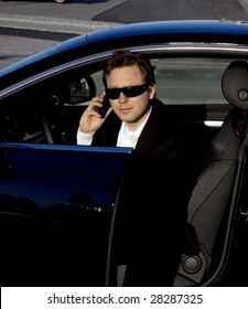 A stylish business executive in a German luxury car. He is talking on his cell phone while getting out of the car.