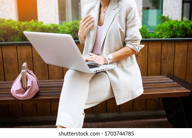 Stylish business lady working outdoor with her laptop. Freelancer working with pc in summer city. Fahionable female manager sit on the bench in the city park and typing.