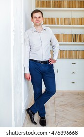 Stylish business man in white shirt and trousers, standing against the wall, against the background of shelves of books