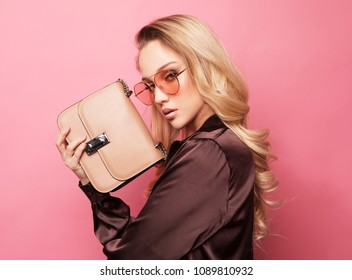 Stylish business woman in blouse and pants posing on pink background.
