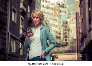 Stylish business woman texting in front of the office building