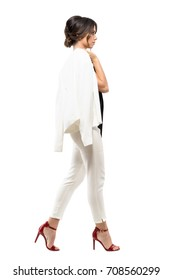 Stylish business woman in white suit walking and carrying jacket over shoulder. Side view. Full body length portrait isolated on white background