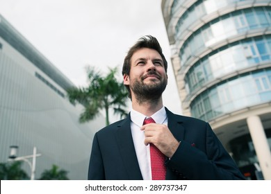 Stylish businessman adjusting necktie while standing outdoors