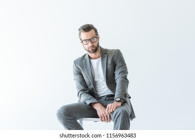 stylish businessman in gray suit sitting on chair, isolated on white