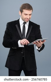 Stylish businessman is happy by the news he is reading on his tablet pc