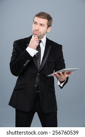 Stylish businessman is intrigued by the news he is reading on his tablet pc