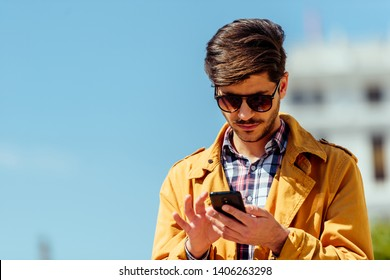 Stylish businessman is standing outdoors and looking at his mobile, calling for a taxi ride, e-hailing