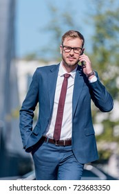 stylish businessman in suit using smartphone