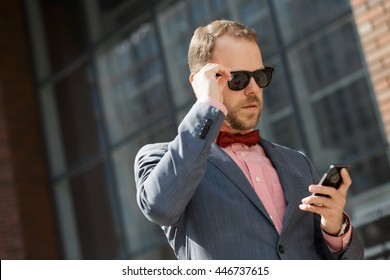 Stylish businessman in sunglasses using smartphone at city downtown