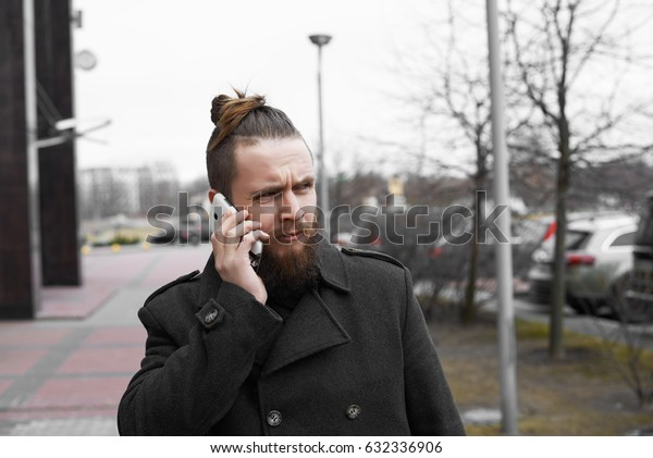 Stylish businessman talk by phone with colleague abouth finance plan. Modern guy standing in street in spring or autumn time and call friend about weekend. Young businessman having mobile conversation